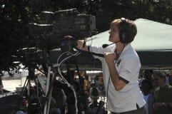 Camerwoman de la TV que graba una demostración fotografía de archivo libre de regalías