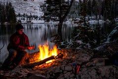 Camfire chaud d'hiver avec un homme se chauffant Photographie stock libre de droits