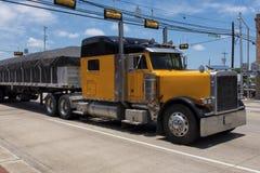 Camión amarillo en una carretera que cruza una pequeña ciudad americana Fotos de archivo libres de regalías