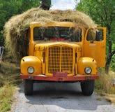 Camión amarillo viejo que es cargado con la paja fotografía de archivo libre de regalías
