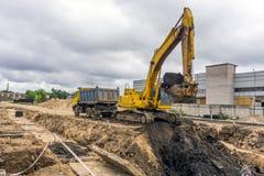 Camión amarillo y excavador amarillo foto de archivo libre de regalías