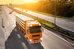 Camión anaranjado en la falta de definición de movimiento en la carretera Imagen de archivo libre de regalías