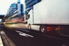 Camión blanco que se mueve rápidamente en el camino en una ciudad moderna con efecto luminoso imagen de archivo libre de regalías