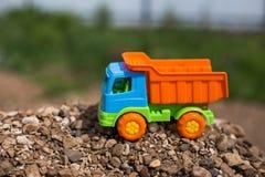 Camión coloreado del juguete con la arena y las piedras Foto de archivo libre de regalías