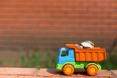 Camión coloreado del juguete con la arena y las piedras Fotografía de archivo