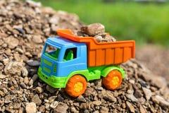 Camión coloreado del juguete con la arena y las piedras Foto de archivo