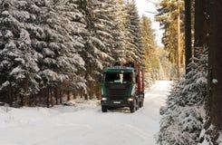 Camión con el camino del inicio de sesión en bosque en invierno Fotografía de archivo libre de regalías