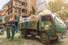 Camión de basura que recoge la basura en la ciudad fotos de archivo