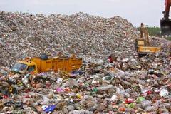 Camión de basura y retroexcavadora que trabajan en descarga de basura municipal en l imagen de archivo libre de regalías