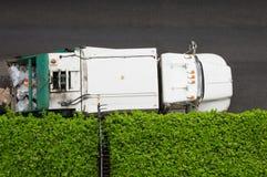 Camión de basura y seto verde Imagen de archivo libre de regalías