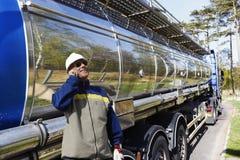 Camión de combustible y trabajador de la refinería en el casco de protección Fotografía de archivo