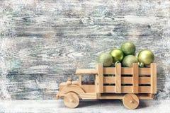 Camión de madera del juguete con las bolas de una Navidad del verde en la parte posterior en un g Fotografía de archivo libre de regalías