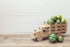 Camión de madera del juguete con las bolas de una Navidad del verde en la parte posterior en whi Fotografía de archivo libre de regalías