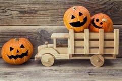 Camión de madera del juguete con las calabazas de Halloween en la parte posterior en un backgr Imagenes de archivo