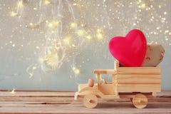 camión de madera del juguete con los corazones delante de la pizarra Foto de archivo