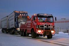 Camión de remolque lleno que es remolcado a lo largo del camino Foto de archivo