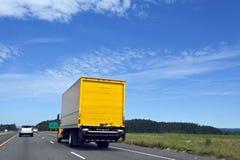 Camión de reparto amarillo en la carretera debajo del cielo azul imagen de archivo