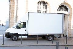 Camión de reparto blanco con el panel en blanco en la calle de la ciudad fotografía de archivo libre de regalías