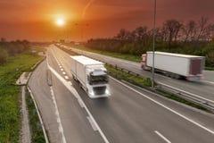 Camión de reparto en la falta de definición de movimiento en la carretera en la puesta del sol imagen de archivo libre de regalías