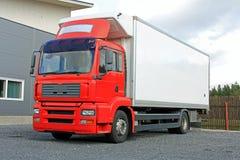 Camión de reparto rojo por Warehouse Imágenes de archivo libres de regalías