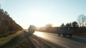 Camión de 18 ruedas en el camino con puesta del sol en el fondo El camión de reparto grande se está moviendo hacia el sol ponient metrajes
