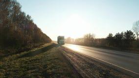 Camión de 18 ruedas en el camino con puesta del sol en el fondo El camión de reparto grande se está moviendo hacia el sol ponient almacen de metraje de vídeo