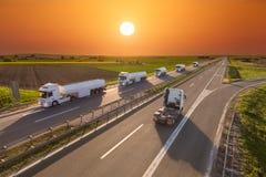 Camión del depósito de gasolina de la entrega en la falta de definición de movimiento en la carretera en la puesta del sol Imagen de archivo