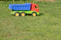 Camión del juguete en la hierba, juguete abandonado Imágenes de archivo libres de regalías
