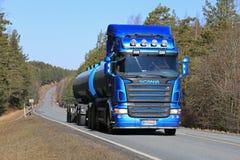 Camión del tanque azul de Scania en el camino rural en la primavera Imagen de archivo