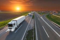Camión del transporte de la entrega en la falta de definición de movimiento en la carretera en la puesta del sol Foto de archivo