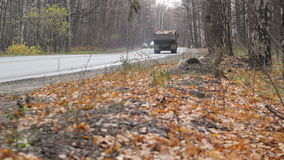 Camión en la carretera del autobahn del campo que se aleja a través de bosque del otoño almacen de video