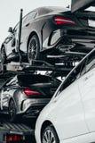 Camión grande del portador de coche de los coches alemanes del nuevo deporte de lujo para la entrega del lote a la representación imágenes de archivo libres de regalías