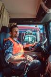 Camión o conductor de camión que se sienta en la cabina de su vehículo imagen de archivo libre de regalías