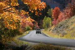 Camión que conduce abajo del camino del país en otoño de la caída Imagen de archivo