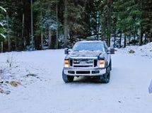 camión 4x4 que deriva en el camino de la nieve del invierno en bosque Imagen de archivo