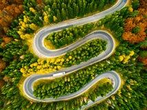 Camión que enrolla encima de su manera en un camino curvy con otoño coloreado Foto de archivo libre de regalías
