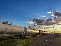 Camión que espera en la travesía tren en la puesta del sol imagen de archivo