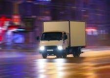 Camión que mueve encendido la ciudad de la noche Imagen de archivo