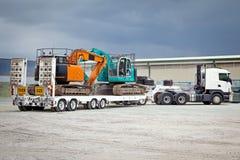 Camión que remolca los excavadores hidráulicos Foto de archivo libre de regalías