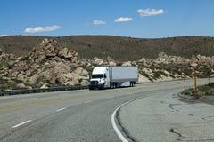 Camión que viene cuesta abajo en la carretera de cuatro carriles Imagen de archivo libre de regalías