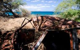 Camión rojo abandonado en árboles cerca de la playa de Waialea Fotografía de archivo