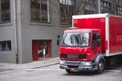 Camión rojo de la pequeña caja semi para la entrega en las calles de la ciudad Fotos de archivo