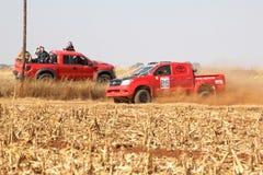 Camión rojo de la reunión de Toyota que pasa espectadores rojos el camión en Roa polvorienta Foto de archivo libre de regalías