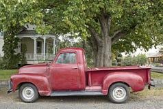 Camión rojo del vintage delante del hogar victoriano Fotos de archivo libres de regalías