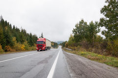 Camión rojo en la pista en otoño fotografía de archivo