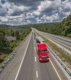 Camión rojo grande en la carretera larga de la montaña Imagen de archivo
