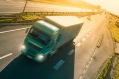 Camión verde en la falta de definición de movimiento en la carretera Fotos de archivo libres de regalías