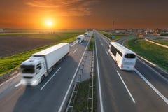 Camión y autobús blancos en la falta de definición de movimiento en la carretera en la puesta del sol Fotos de archivo