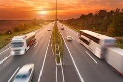 Camión y autobús en la autopista en la puesta del sol Foto de archivo libre de regalías