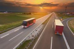 Camión y autobús en la falta de definición de movimiento en la autopista en la puesta del sol Foto de archivo